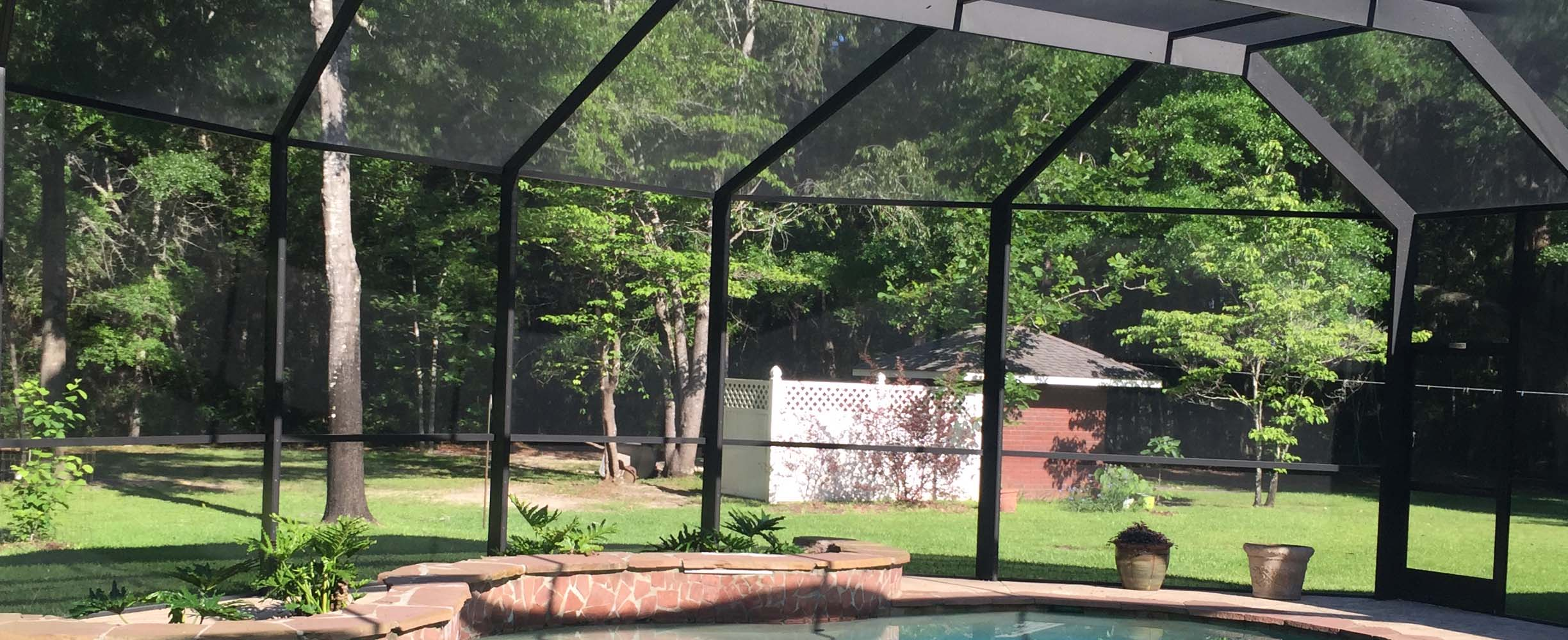 Pool enclosure with black aluninum and modern materials and structure that stands typical Southern high winds and weather