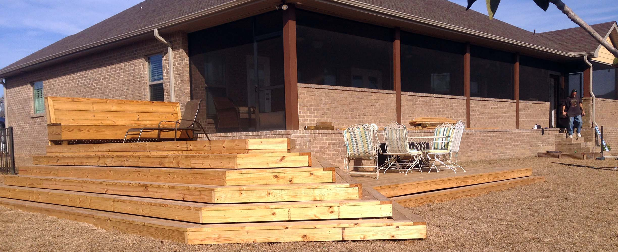 Wooden dech with wooden steps adding functionality to a house while making the garden more beautiful and prectical